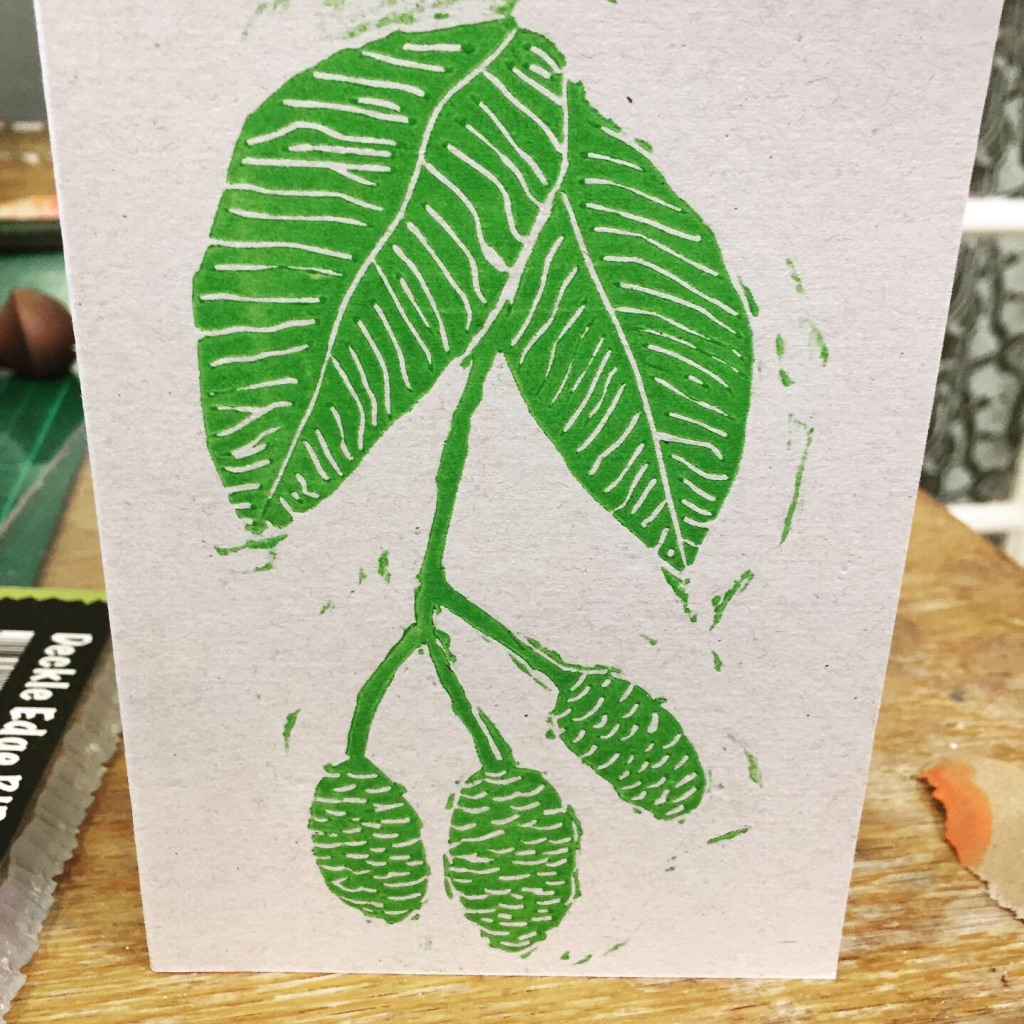 Photo of an A6 card printed with green ink onto recycled card.