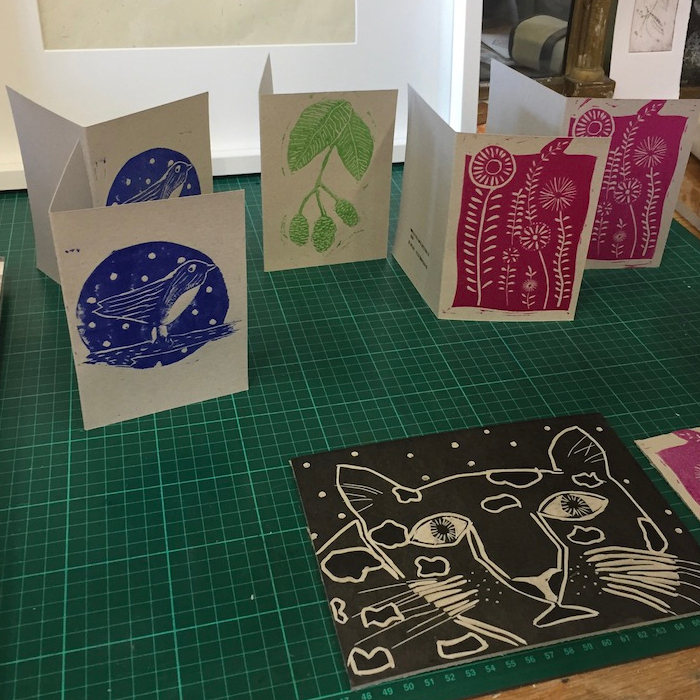 Photo of 4 very different card designs at a family linocut print workshop hosted by Skirrid Print Studio