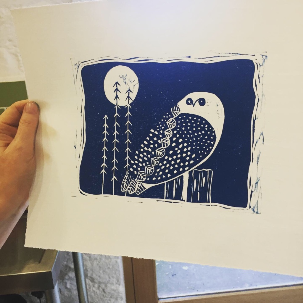 Student holding up her workshop piece - linocut print of owl and moon